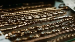 luxury gold jewelry chains, bracelets background, selective focus. Stylish beautiful bijouterie
